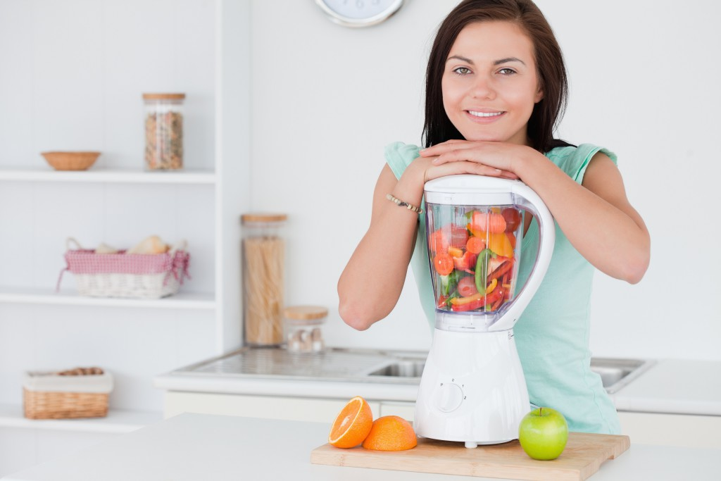 Brunette posing with a blender